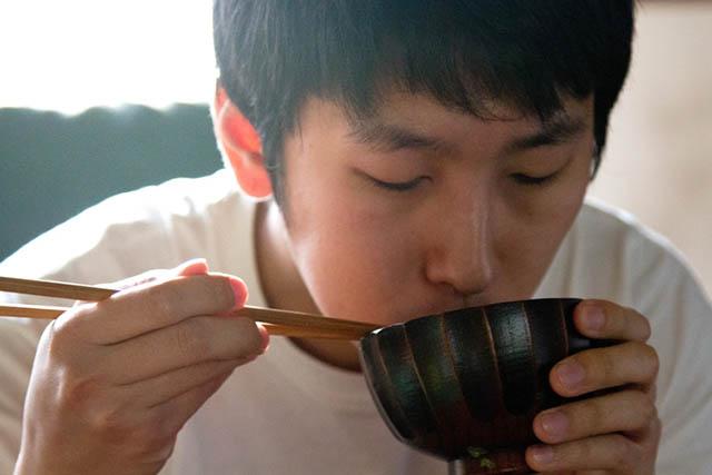 味噌汁を飲む人