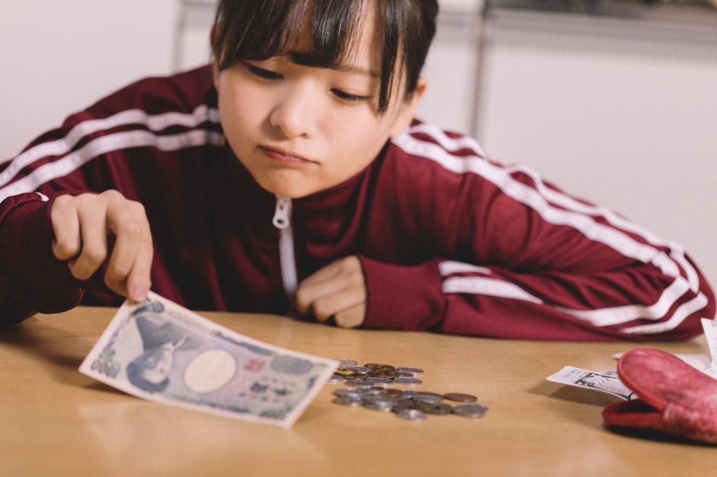 お金をつまんでいる女性