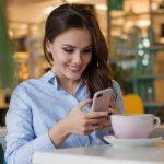 カフェで携帯を見つめる女性