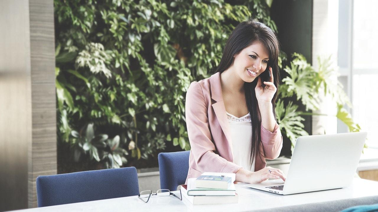 PCを見ながら電話している女性