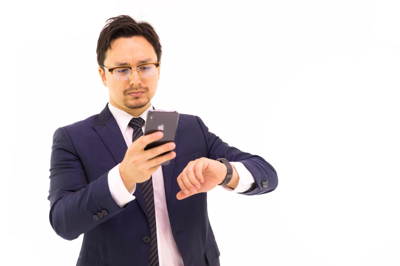 腕時計を見ながらスマホを見る男性