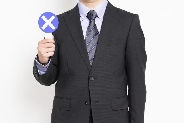 バツのプラカードを持つ男性