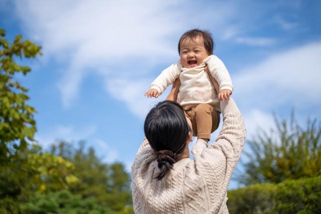 公園で赤ちゃんと遊ぶ母親