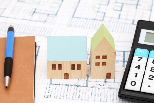 図面と電卓と家の置物